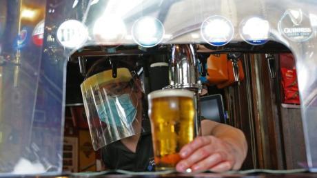 Ein Barkeeper zapft in London mit Mundschutz und Visier ein Glas Bier.