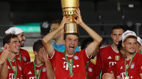 Münchens Thomas Müller hält die Trophäe nach dem Spiel hoch.