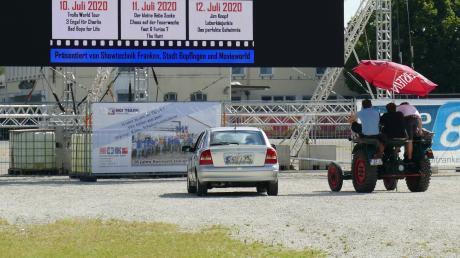 Ein Auto und ein Traktor stehen auf der Kaiserwiese. Viele Besucher haben ihre Autokino-Tickets kurzfristig storniert.
