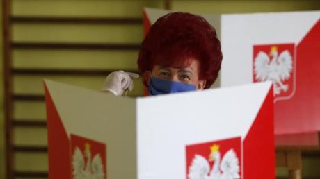 Mit Mundschutz, aber frisch toupiert: Eine Wählerin bei der Stimmabgabe in  Rybnik. Polen entscheidet in einer Stichwahl über den Präsidenten.