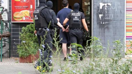 Polizeibeamte führen einen mit Handschellen gefesselten Mann in ein Haus in Berlin-Kreuzberg.