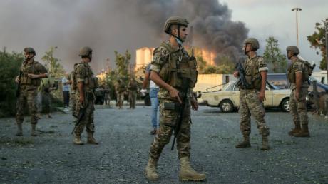 In der libanesischen Hauptstadt Beirut ist es zu einer schweren Explosion gekommen. Die Hintergründe blieben zunächst unklar. Soldaten stehen in der Nähe des Ortes einer Explosion am Hafen.