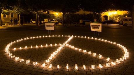 Greenpeace-Ehrenamtliche haben ein Peace-Zeichen aus Kerzen auf dem Elias-Holl-Platz aufgestellt.
