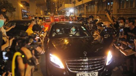 Jimmy Lai (Vordersitz, r) wird beimVerlassen des Polizeireviers von mehreren Dutzend Anhängern der Demokratiebewegung bejubelt.