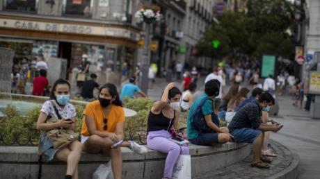 Menschen mit Masken in der Innenstadt von Madrid: Das Auswärtige Amt warnt wegen der Corona-Pandemie nun auch vor Reisen inSpaniens Hauptstadt.