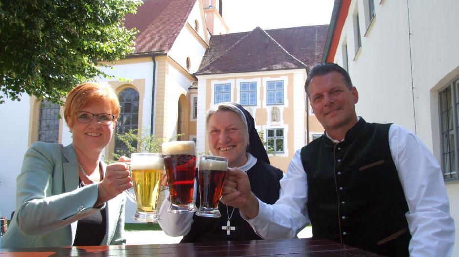 Die Brauerei Ustersbach hat für die Abtei Oberschönenfeld ein eigenes Bier gebraut. Mit dem bereits vorhandenem dunklen und dem neuen hellen Gerstensaft stoßen an: (von links) Brauereichefin Stephanie Schmid, Äbtissin Gertrud Pesch und Klosterstüble-Gastronom Michael Haupt.