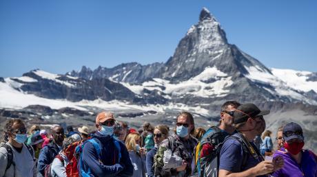 Touristen warten vor dem Matterhorn auf den Zug der Gornergratbahn.