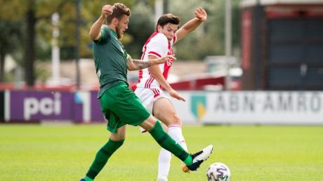 Jeffrey Gouweleeuw (in Grün) im Zweikampf mit Ajax-Spieler Jurgen Ekkelenkamp.  Gouweleeuw wird Kapitän des FC Augsburg werden.