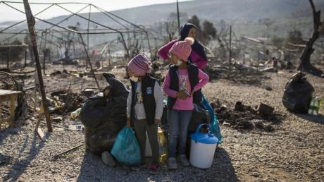 Eine Familie steht innerhalb des ausgebrannten Flüchtlingslagers Moria. Mehrere Brände haben das Lager fast vollständig zerstört. Augsburg will wie viele andere Kommunen in Deutschland helfen.