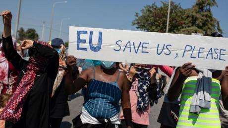 """""""EU rette uns, bitte"""" steht auf einem Schild, das Flüchtlinge aus Moria bei einem Protest auf den Straßen von Lesbos tragen."""