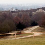 Vorne ist der begrünte Teil des Müllbergs mit Wiesen und Büschen zu sehen, im Hintergrund der noch aktive Bereich der Deponie.