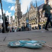 Eine getragene Mundschutzmaske liegt in der Münchener Innenstadt auf dem Gehweg. In der bayerischen Landeshauptstadt gelten ab Donnerstag verschärfte Kontaktbeschränkungen sowie eine generelle Maskenpflicht in Teilen der Altstadt.