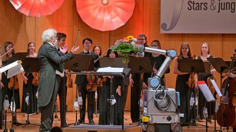 Ein Roboter ist der heimliche Star dieses Festivals der Nationen, an dem es an echten Stars wie immer nicht mangelt. Hier überreicht der Roboter Blumen an Dirigent Christoph Adt.