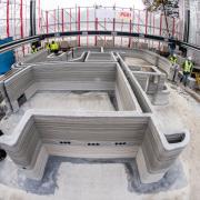 Mitarbeiter des Bauunternehmens stehen in dem eingerüsteten Bauplatz, wo bereits mehrere Schichten Beton von dem 3D-Drucker aufgetragen wurden.