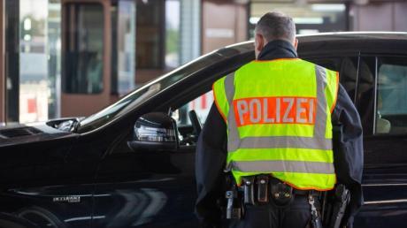 Ein Beamter der Bundespolizei kontrolliert an einem Grenzübergang einen Autofahrer.