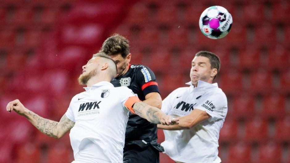Leverkusens Lucas Alario(M.) und Augsburgs Jeffrey Gouweleeuw (l.) sowie Raphael Framberger versuchen an den Ball zu kommen.