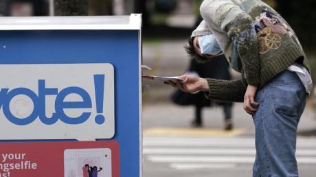 In der US-Stadt Seattle wirft ein Frühwähler seinen Stimmzettel in eine Wahlurne.