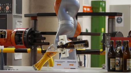 Der sensitive Leichtbauroboter LBR iiwa für eine sichere Mensch-Roboter-Kollaboration schenkt ein Weißbier ein.