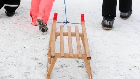 Winterurlauber gehen mit einem Schlitten zu einer Rodelbahn.