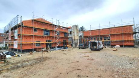 Das Bild zeigt einen Teil des neuen Kindergartens von der Bauernstraße aus mit einer roten Fassade. Dies ist aber nur eine Schutzfolie, die auf der Außenisolierung aufgebracht ist.