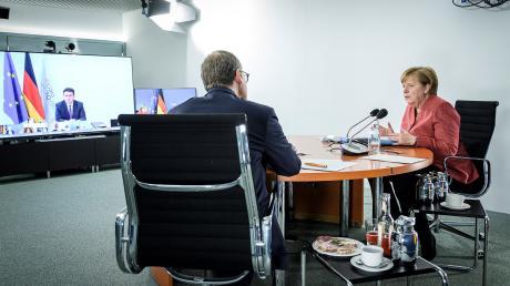 Tief in der Diskussion: Berlins Regierender Bürgermeister Michael Müller und Bundeskanzlerin Angela Merkel konferieren über eine Videoschalte mit der Bundesregierung und den übrigen Ministerpräsidenten.