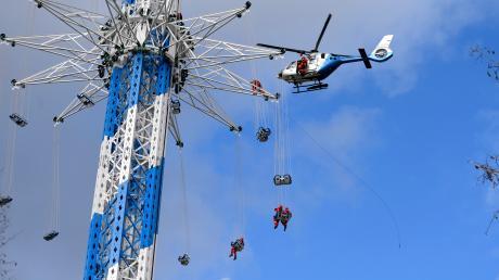 Alles nur eine Übung: Höhenretter der Berufsfeuerwehr Augsburg gelangen über die Seilwinde des Polizeihubschraubers zu Patienten im Allgäuflieger in 100 Meter Höhe.