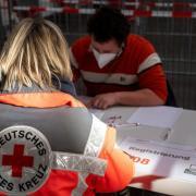 21.11.2020, Baden-Württemberg, Ulm: Eine Mitarbeiterin des Deutschen Roten Kreuzes simuliert die Registrierung im Messezentrum. Das Deutsche Rote Kreuz probte den Ablauf zur  Impfung eines Corona-Impfstoffs in dem neben weiteren für das Land Baden-Württemberg geplanten Impfzentren. In Ulm sollen pro Stunde bis zu 120 Menschen geimpft werden können. Foto: Stefan Puchner/dpa +++ dpa-Bildfunk +++