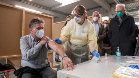 Sozialminister Manne Mucha (Grüne) lässt sich im Ulmer Messezentrum von Notfallsanitäterin Dorothea Gansloser im Beisein von Winfried Kretschmann den Ablauf einer Corona-Impfung demonstrieren.