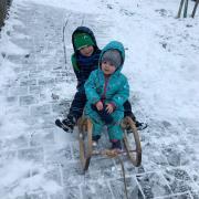 Lorenz und Rosina Egger sind nach dem Schneeschippen auf dem Weg zum Kindergarten mit dem Schlitten.