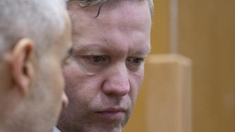 Der Hauptangeklagte Stephan Ernst steht mit seinem Verteidiger hinter der Anklagebank.