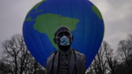 Auch EU-Gründervater Robert Schuman trägt nun Maske - hinter ihm demonstrieren Greenpeace-Aktivisten für eine bessere EU-Klimapolitik.