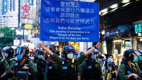 """Ein Polizist warnt Demonstranten: """"Löst euch auf, oder wir wenden Gewalt an."""" In Hongkong richten sich Proteste gegen ein Sicherheitsgesetz."""