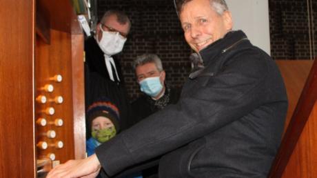 Organist Wolfgang Reiber bringt die Orgel wieder zum Klingen. Über seine Schultern schauen Pfarrer Leander Sünkel (links), Felix (Mitte) und Kirchenvorstand Rudolf Schneider (rechts).