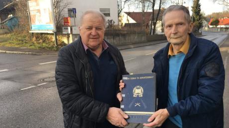 Heimatforscher Johann Weber (rechts) übergibt die Bücher an Dieter Bordon. An diesem Platz in Mering befand sich nach dem Krieg die Panzersperre. Weber war Augenzeuge damals.