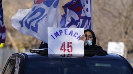 Ein Mann hält in Denver ein Schild aus dem Auto, das die Amtsenthebung von Präsident Donald Trump fordert.