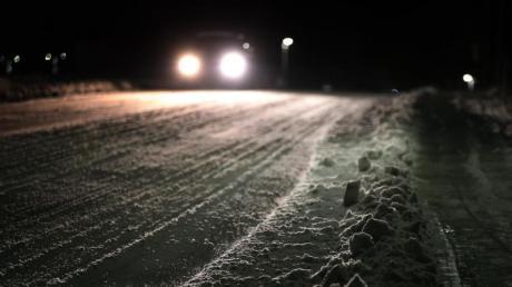 Ein Auto fährt am frühen Morgen über eine schneebedeckte Straße im südbayrischen Marktoberdorf.
