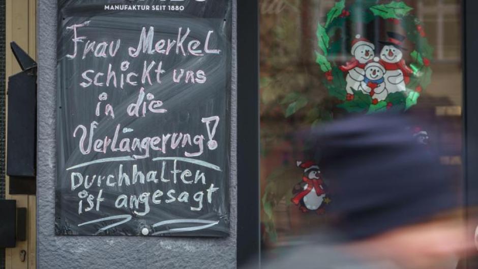 """""""Frau Merkel schickt uns in die Verlängerung! Durchhalten ist angesagt!"""" steht auf einer Tafel neben einem geschlossenen Geschäft im hessischen Friedberg."""