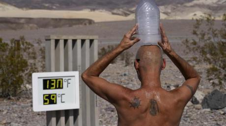 Ganz schön heiß:Ein Mann kühlt sich im «Death Valley»-Nationalpark im US-Bundesstaat Arizona mit einer mit Eiswasser gefüllten Plastikflasche auf dem Kopf ab.