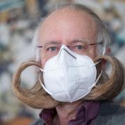 Jürgen Burkhardt, Bartträger und mehrfacher Bart-Weltmeister, demonstriert das Tragen einer FFP2-Schutzmaske.