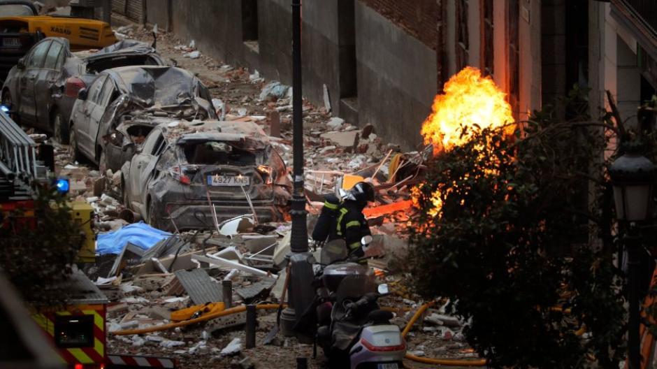 Los bomberos trabajan junto a un edificio dañado en la calle Toledo después de una explosión.