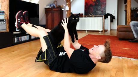 Katzen halten nichts von sportlicher Betätigung. Bevor Tina Schüssler die Bauchmuskeln trainiert flüchtet die pechschwarze Medy.