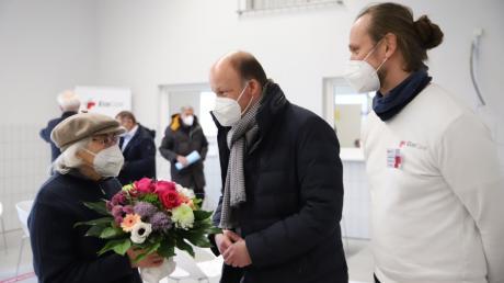 Landrat Martin Sailer (Mitte) und Lauritz Bahnemann, Ärztlicher Leiter des Impfzentrums in Gablingen, übergeben Kunigunde Haas aus Bobingen einen Blumenstrauß. Die Seniorin hat die 10.000. Impfung im Landkreis Augsburg erhalten.