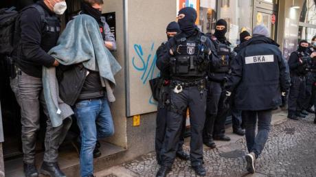 Ein Mann wird bei einer Razzia, mit einer Decke über dem Kopf, von der Polizei abgeführt. Mit einer Großrazzia ist die Polizei am Donnerstag gegen Clankriminalität in Berlin und Umgebung vorgegangen.