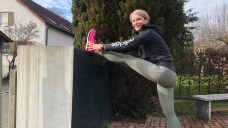 Hoch das Bein! Nachdem sie den Müll entsorgt hat, turnt Fitness- und Gesundheitstrainerin Andrea Michel am Tonnenhäuschen.