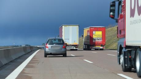 Zwei Lastwagen fahren auf der A8 während eines Überholvorgangs nebeneinander her.