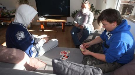 Tanja Schiebler spielt mit zwei Jugendlichen Karten im Wohnzimmer. Die Beiden haben es sich auf dem neuen Sofa bequem gemacht.
