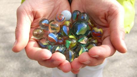 Mit Glasmurmeln gibt es verschiedene Spielvarianten. Gefragt sind dabei vor allem Geschicklichkeit.