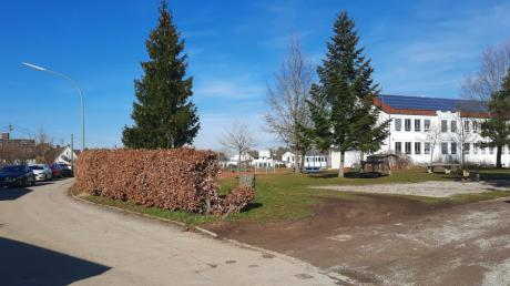 Das Bild zeigt links die beengte Kinderheimstraße mit parkenden Autos und der Buchenhecke, die weichen muss. An der Stelle wird ein Streifen für sechs Parkplätze geschaffen.
