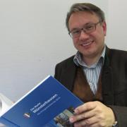 Der CSU-Bundestagsabgeordnete Dr. Georg Nüßlein 2012 mit der Chronik seines Heimatortes Münsterhausen.