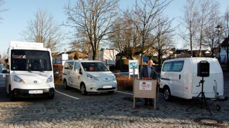 Kleinaitingens Bürgermeister Rupert Fiehl vor seiner Elektrofahrzeugflotte, links der Bürgerbus, in der Mitte das E-Auto des Seniorenfahrdienstes und rechts der Busanhänger.